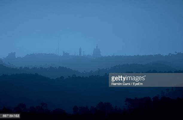 distant view of sagrat cor church on mountain against sky - sagrat cor stock pictures, royalty-free photos & images