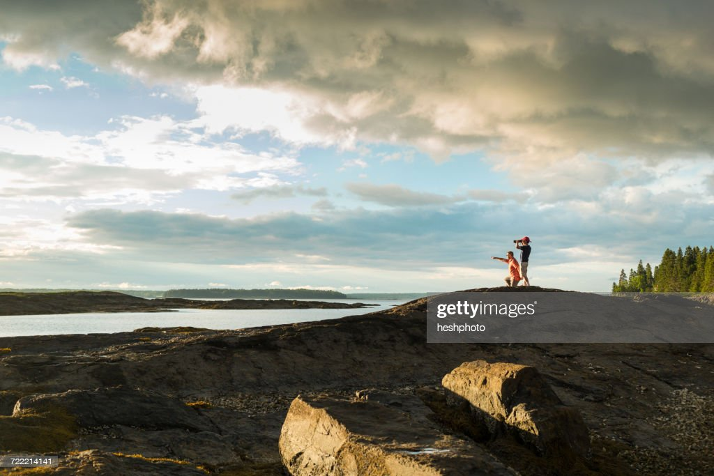 Distant view of senior man and son looking through binoculars at coast of Maine, USA : Stock Photo