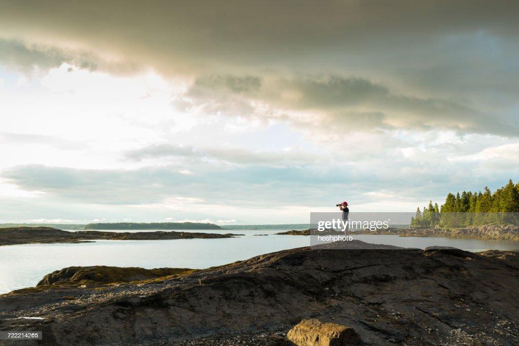 Distant view of senior man looking through binoculars at coast of Maine, USA : Stock Photo