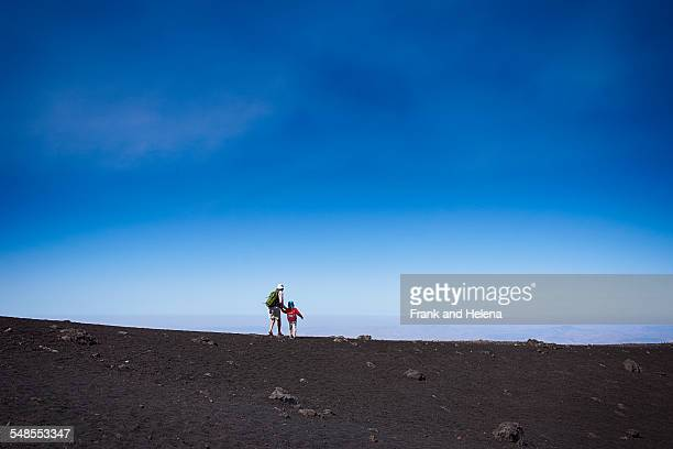 distant view of senior woman and grandson on mount etna, catania, sicily, italy - frank catania stock pictures, royalty-free photos & images