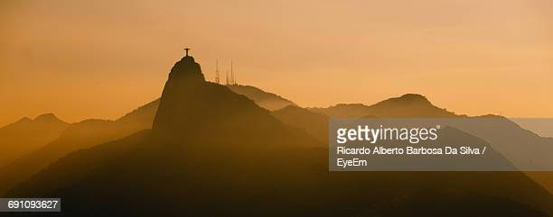 Distant View Of Silhouette Christ The Redeemer Against Orange Sky