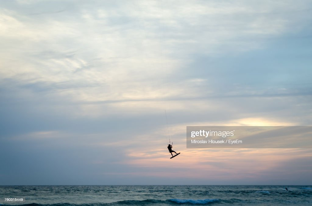 Distant View Of Silhouette Man Kiteboarding Over Sea Against Cloudy Sky : Stock Photo