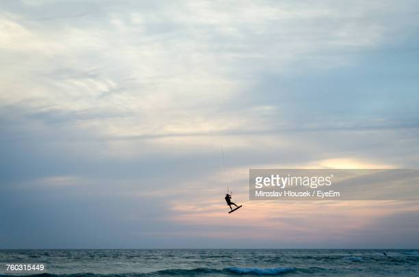 Distant View Of Silhouette Man Kiteboarding Over Sea Against Cloudy Sky