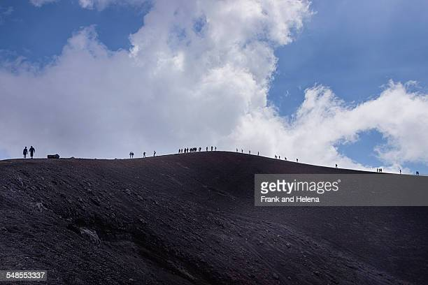 distant view of silhouetted tourists on top of mount etna, catania, sicily, italy - frank catania stock pictures, royalty-free photos & images