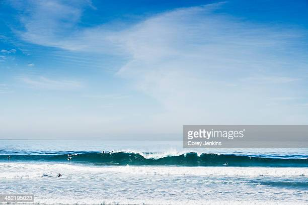 distant view of surfers on ocean wave, black beach, la jolla, california, usa - la jolla stock pictures, royalty-free photos & images