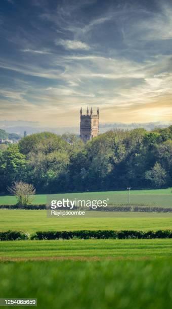 グロスターシャー州サイレンセスターにある洗礼者聖ヨハネ教会の遠景は、周囲の美しいコッツウォルドの風景の上に塔を突き刺しています。 - グロスターシャー ストックフォトと画像