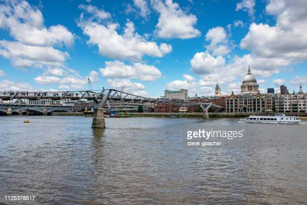distant view of the london millennium footbridge showing pedestrians croosing the river thames. - greater london stock pictures, royalty-free photos & images
