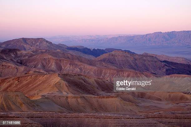 Distant view of the Valley of Arava and the Edomite Heights or mountains of Edom in Jordan from a viewing platform in Eilat Mountains Nature Reserve in south of Israel, within the southern Negev Desert