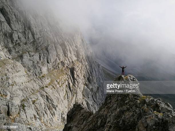 Distant View Of Tourist Standing With Arms Outstretched On Rock In Foggy Weather