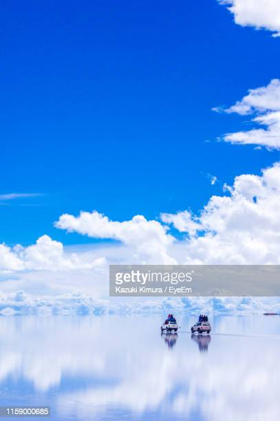 distant view of tourists on cars by lake against blue sky - ウユニ ストックフォトと画像