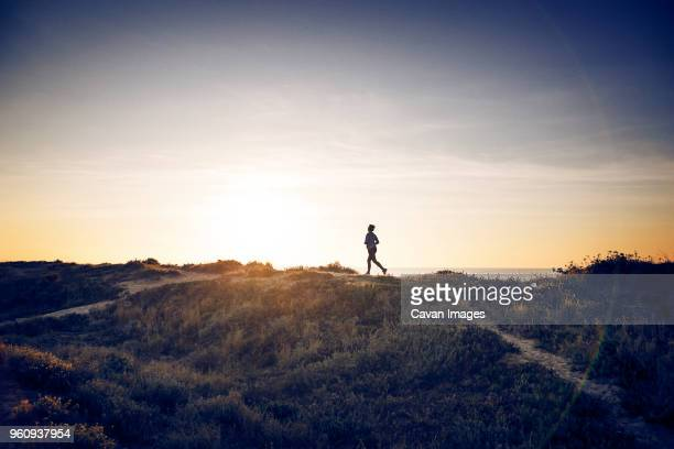 distant view of woman jogging on field against sky - distant stock pictures, royalty-free photos & images