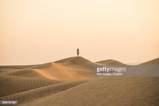 Distant View Of Woman Standing On Sand Dune At Desert Against Clear Sky