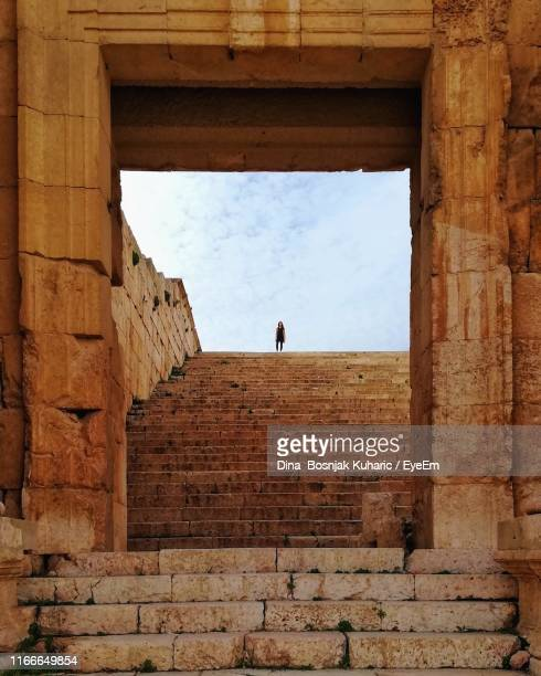 distant view of woman standing on staircase against sky - jordan middle east stock pictures, royalty-free photos & images