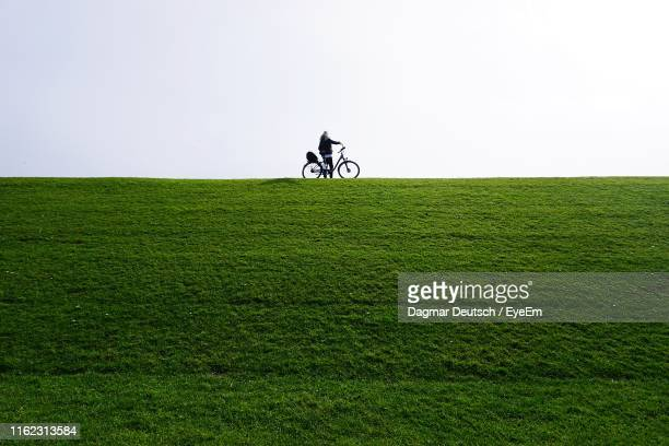 distant view of woman with bicycle standing on grassy land against clear sky - levee stock pictures, royalty-free photos & images