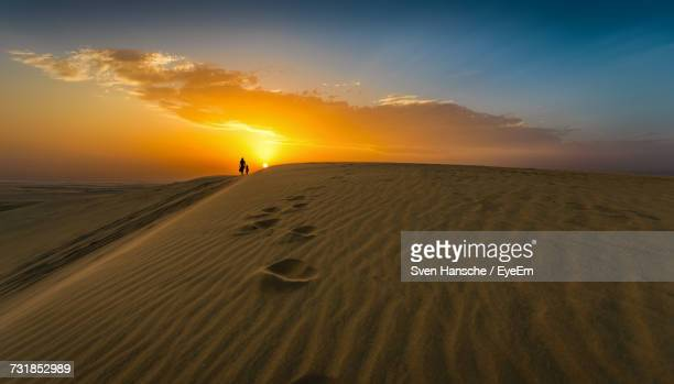 distant view of woman with child walking on desert against sky during sunset - doha stockfoto's en -beelden