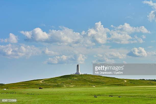 distant view of wright brothers national memorial on field against sky - kitty hawk north carolina stock pictures, royalty-free photos & images