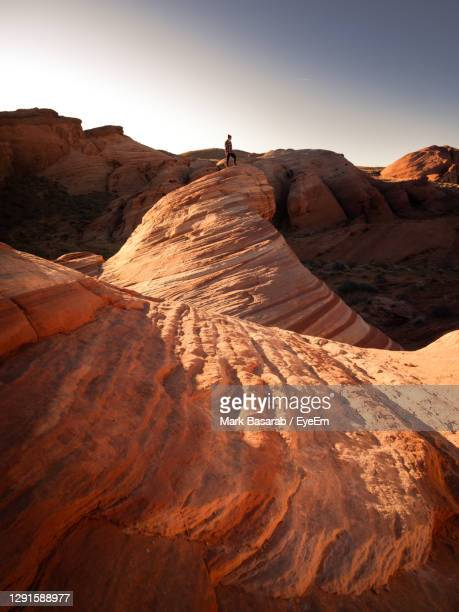 distant view of young man standing on rock formation against sky - nevada stock pictures, royalty-free photos & images