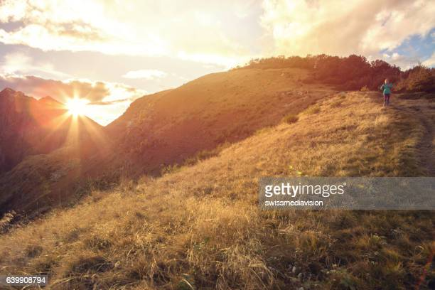 Distant woman hiking moving down hill