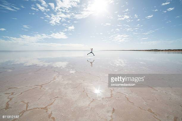 distant woman jumping on salt lake - south australia stock pictures, royalty-free photos & images