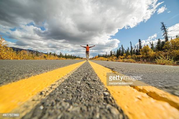 Distant woman standing on road arms outstretched