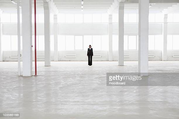 Distant woman stands in empty warehouse