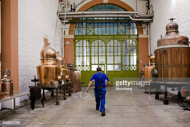 A distiller walks between vintage alambic stills inside the absinthe distillery operated by Pernod Ricard SA in Thuir France on Wednesday June 8 2016...