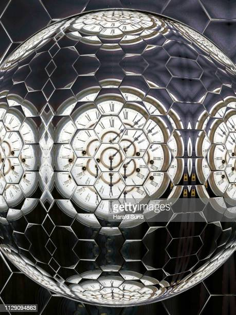 Distorted appearing vintage antique grandfather clock face with Roman numeral numbers and hour and second hands multiply reflected in a hexagon sphere glass shapes.
