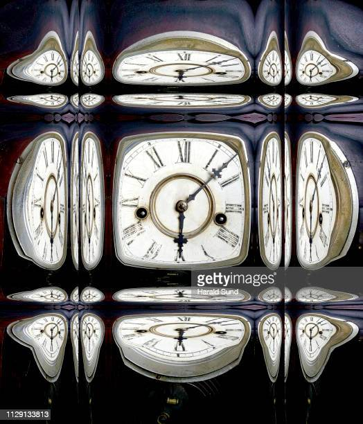 Distorted appearing vintage antique grandfather clock face with Roman numeral numbers and hour and second hands multiply reflected in glass cubes.