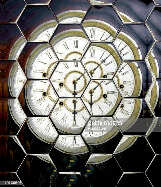 Distorted appearing vintage antique grandfather clock face with Roman numeral numbers and hour and second hands multiply reflected in hexagon glass shapes.