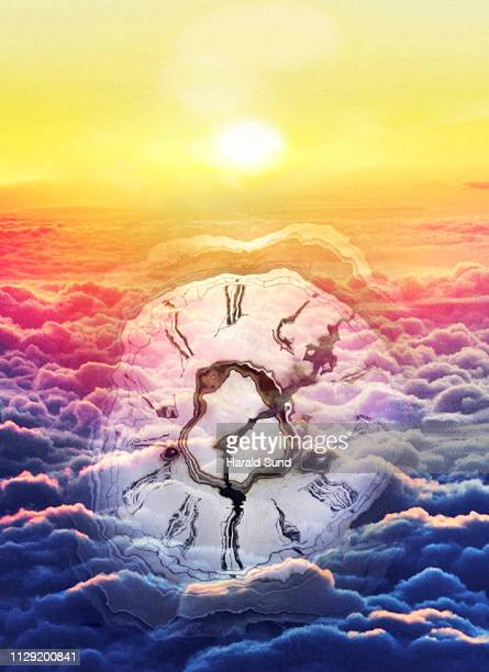 Distorted appearing vintage antique grandfather clock face with Roman numeral numbers and hour and second hands floating in a sea of sun lit clouds.