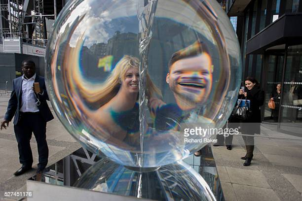 Distorted faces of a couple seen through Petroc Sesti's art instillation called Time Fold in Great Helen's Square in the City of London Passersby...