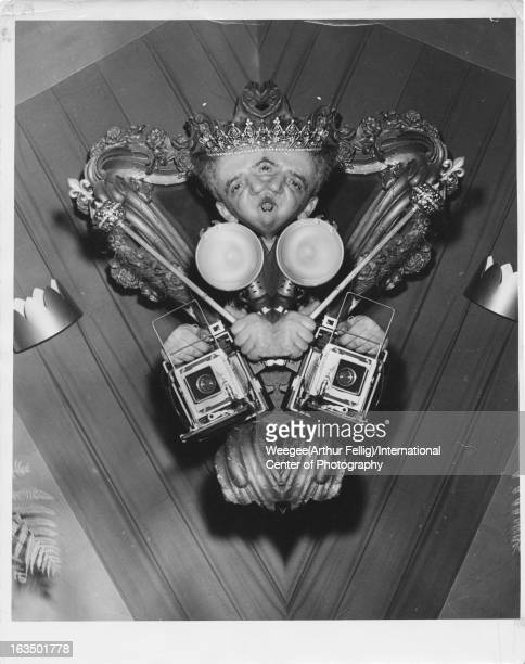 Distorted selfportrait by American photographer Weegee wearing crown and smoking cigar while holding a Speed Graphic Camera New York New York 1956...