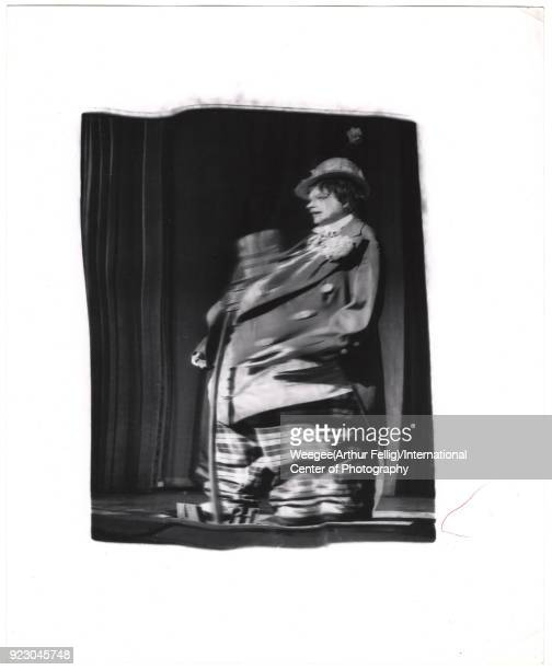 Distorted view of American actress and musician Judy Garland in a clown costume onstage during the opening performance of her 'All Star Variety Show'...
