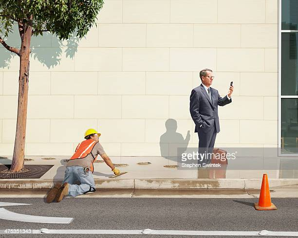 Distracted businessman standing in wet cement