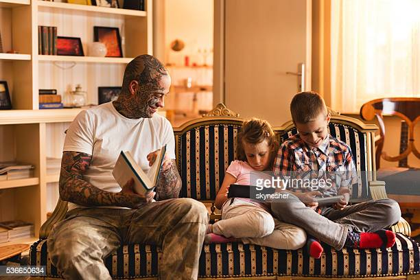 Distracted children ignoring their father while using wireless technology.