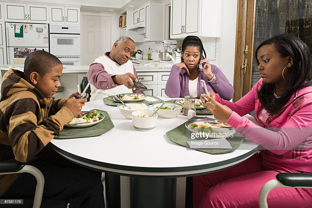Distracted family at the dinner table : Stock Photo