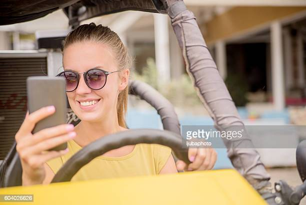 Distracted  teenage girl or woman texting while driving a car