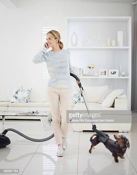 Distracted woman vacuuming dog