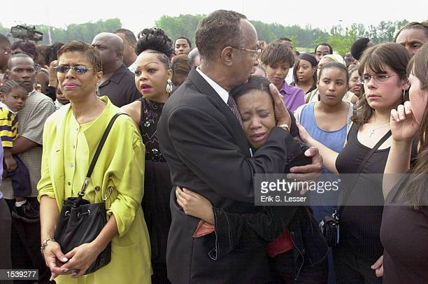 A distraught fan is comforted by a church deacon waiting in line to attend the public funeral of singer Lisa Left Eye Lopes at the New Birth...