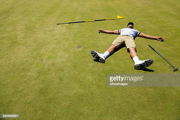 Distraught golfer lying on putting green.
