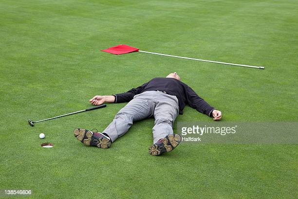 A distraught golfer lying on putting green with ball at the edge of hole