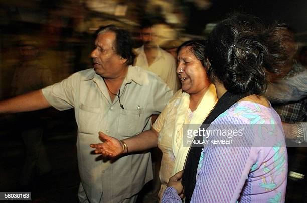 A distraught Indian woman is escorted to a waiting ambulance by bystanders following a series of bomb blasts in New Delhi late 29 October 2005 At...