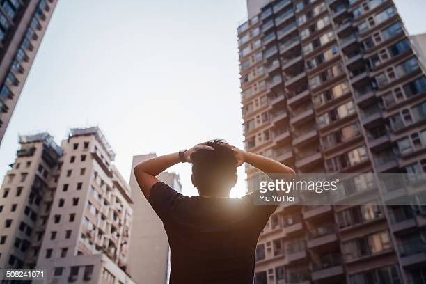 Distraught man holding his head in front of city