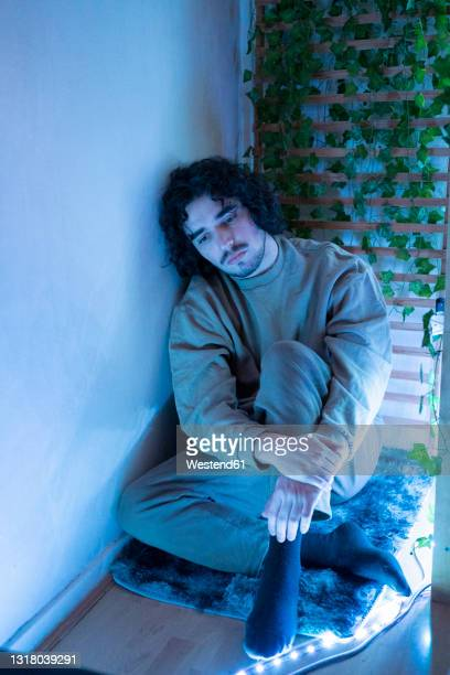 distraught man sitting by wall at home - sadness stock pictures, royalty-free photos & images
