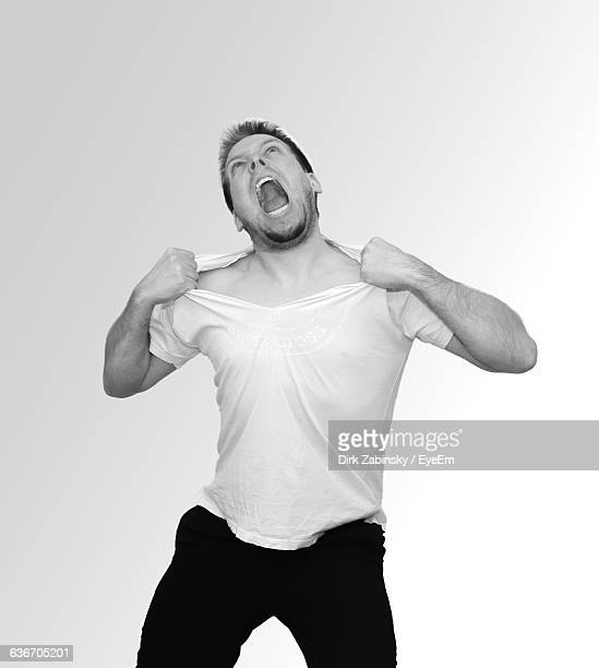 Distraught Man Tearing T-Shirt Against White Background