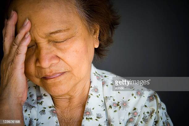 Distraught, pained older woman, eyes closed, hand to brow