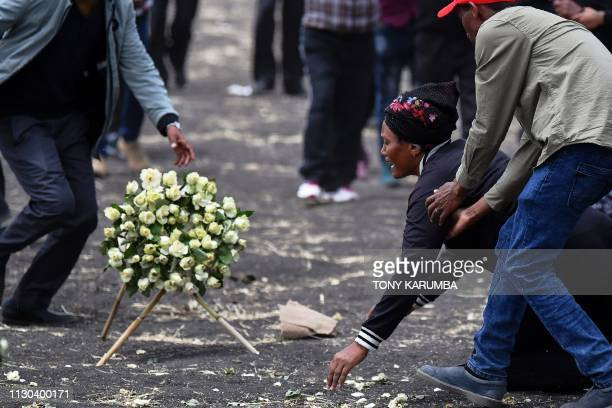 A distraught relative is assisted after she is overcome at the crash site of the Ethiopian Airlines operated Boeing 737 MAX aircraft at Hama...