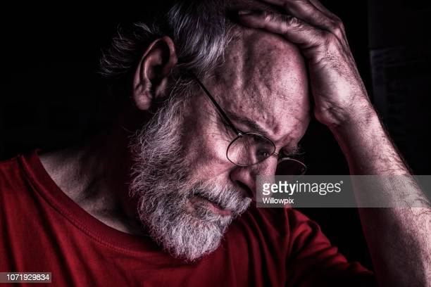 distraught senior adult man holding head - pain stock pictures, royalty-free photos & images
