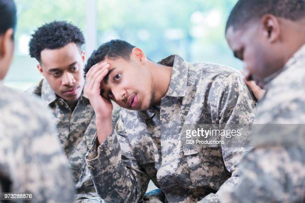 distraught solider during support group meeting - soldier praying stock photos and pictures