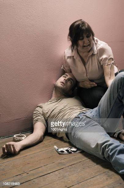 distraught woman kneeling beside overdosed young man with syringe - dead women stock photos and pictures